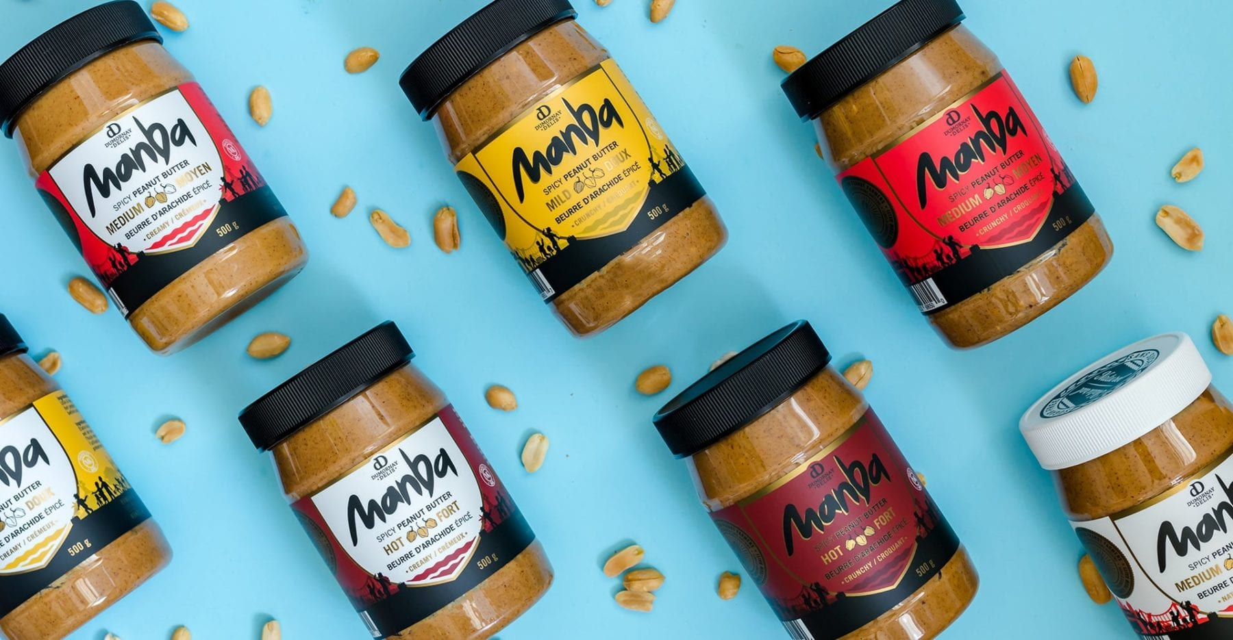 Various Jars of Manba spicy peanut butter on blue background